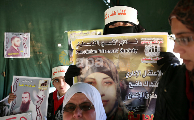 Palestinians hold portraits of jailed compatriots as they join a protest in solidarity with Hana Shalabi, a female Palestinian prisoner jailed in Israel who has been on hunger strike for 19 days, in the West Bank city of Hebron, 08 March 2012. Photo by Ismail Youssef