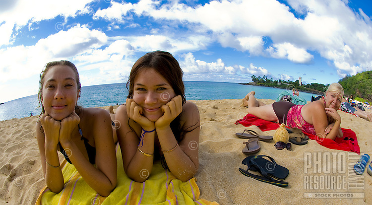 Two young sisters and a friend at Waimea Bay