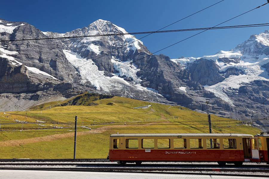 Rail car sits on tracks below the Jungfrau at Kleine Scheidegg train station, Bernese Oberland, Switzerland