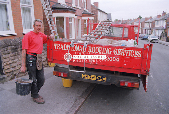 Builder holding bucket of mortar standing next to roofing truck,