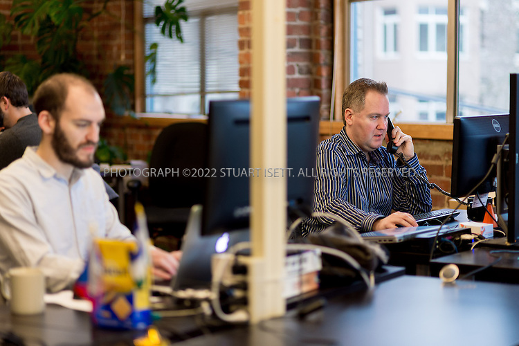 2/28/2014&mdash;Seattle, WA, USA<br /> <br /> Chris Hammersley,  (right), a Seattle based e-commerce executive, working at his desk at Office Nomads, a coworking space in Seattle&rsquo;s Capitol Hill neighborhood.<br /> <br /> Hammersley is based in Seattle, but his company HQ is in Walnut Creek, Ca. and his bosses live in Chicago and Boston. When meetings take place, they can happen anywhere, so Chris uses coworking spaces in those cities and others when he travels for work. <br /> <br /> <br /> Photograph by Stuart Isett. <br /> &copy;2013 Stuart Isett. All rights reserved.