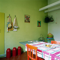 The kitchen is simple, but colourful, with its green walls and blue painted breakfast table and orange painted chairs