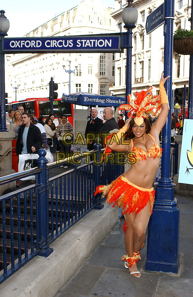 JODIE MARSH.Helps launch the new PETA ad campaign urging tube riders to say no to nuggets. Jodie travelled from Oxford Street to Liverpool Street informing passengers how millions of chickens suffer every year before being slaughtered. .November 7th, 2005 .Ref: BEL.full length orange yellow feather hat bikini top skirt cleavage belly stomach midriff.www.capitalpictures.com.sales@capitalpictures.com.© Capital Pictures.