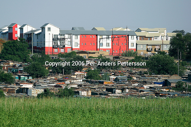 SOWETO, SOUTH AFRICA DECEMBER 17: Newly built flats is seen close to a poor squatter camp on December 17, 2006 in Chris Hani Squatter camp, in Soweto, Johannesburg, South Africa. Thousands of people still live in dire conditions without water or electricity, even after a black run government since 1994. South Africa?s largest township and it was founded about one hundred years to make housing available for black people south west of downtown Johannesburg. The estimated population is between 2-3 million. Many key events during the Apartheid struggle unfolded here, and the most known is the student uprisings in June 1976, where thousands of students took to the streets to protest after being forced to study the Afrikaans language at school. Soweto today is a mix of old housing and newly constructed townhouses. A new hungry black middle-class is growing steadily. Many residents work in Johannesburg but the last years many shopping malls have been built, and people are starting to spend their money in Soweto. .(Photo by Per-Anders Pettersson/Getty Images)..