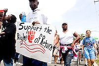 Residents of New Orleans, both current and pre-storm, gather at the levee wall in the Lower 9th Ward on August 29, 2006, the one year anniversary of the levees breaking, to march downtown and protest against what they see is the increased marginalization of their voices.