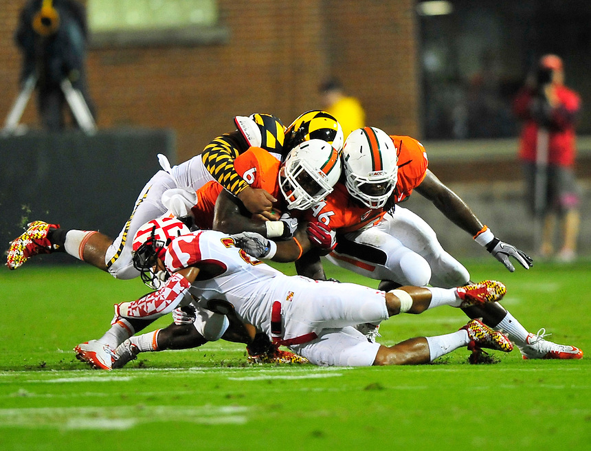 Hurricanes' Lamar Miller is brought down by the Terrapin's defense. Maryland defeated Miami 32-24 during a game at the Byrd Stadium in College Park, MD on Monday, September 5, 2011. Alan P. Santos/DC Sports Box