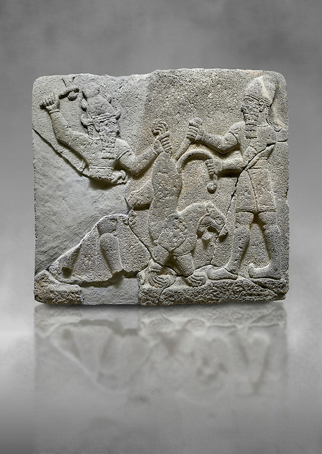 Hittite relief sculpted orthostat stone panel of Herald's Wall Basalt, Karkamıs, (Kargamıs), Carchemish (Karkemish), 900-700 B.C. Anatolian Civilisations Museum, Ankara, Turkey.<br /> <br /> On the right is a bearded human figure with a short skirt; with the dagger in his right hand, he is stabbing the lion standing on his front legs while holding the lion's tail with his left hand. On the left is a bearded god figure with a horned-headdress, who grasps the lion's hind leg while holding the ax over his head with his right hand. <br /> <br /> Against a grey art background.