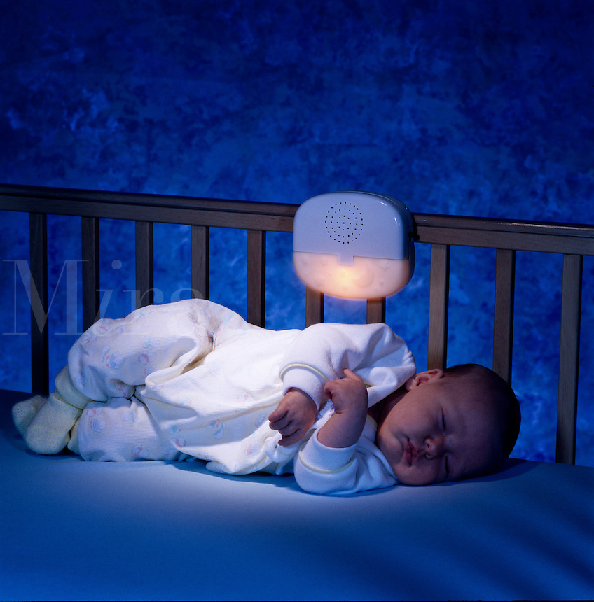 Baby sleeping in crib with nightlite.
