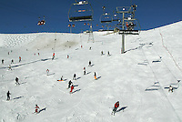 "Switzerland. Valais. Crans Montana. Winter ski resort. CMA ( Crans Montana Aminona) red cable cars and chair lifts are carrying people to the top of the mountain, while other are skiing down  the ""Pas du loup"" slopes on a sunny day with blue sky. Foam protection on the poles of snow cannons. The fog is covering the Rhone valley. © 2005 Didier Ruef"