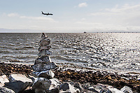 More than a dozen rocks, stacked one on top of the other, pointing skyward, to a plane on final approach to the Oakland International Airport along San Francisco Bay.