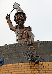 Paul Richardson's 'The Major' metal sculpture of a military gentleman swatting flies, Ipswich, Suffolk, England. On the roof of a public toilet.