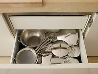 Stainless steel saucepans and colanders are stored out of view in deep kitchen drawers