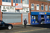 Closed carpet shop and open betting shop, Middleton, Rochdale.