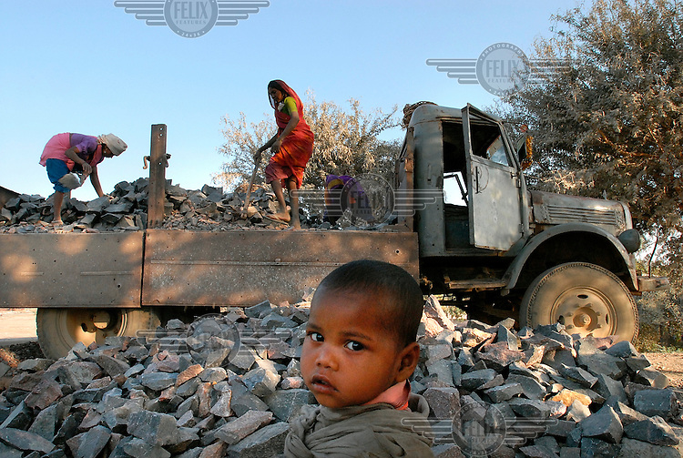 A Dalit child watches his mother as she unloads rocks from a truck at a stone crushing factory. The members of the segregated low-ranking Dalit caste perform the most menial jobs in Hindu society and are considered to be literally 'untouchable'.