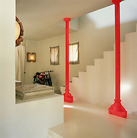 The ultra-modern contrasts with the traditional in the hallway, the red pillars, rescued from the old Marseille train station. A hessian curtain hangs at a small window above the concrete staircase