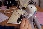 Voodoo doll being held by a female office worker who is sticking pins into the doll dressed in grey suit and grey tie