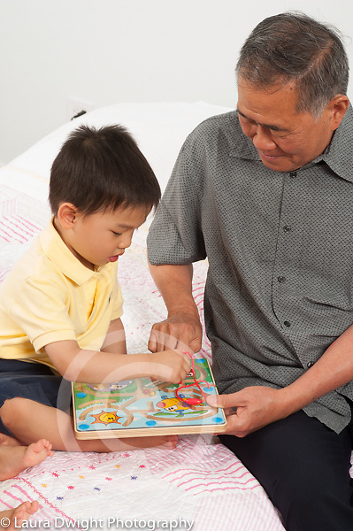 3 year old preschool age boy with grandfather playing with toy puzzle