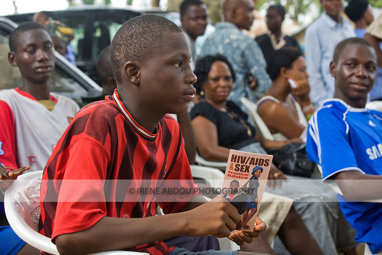 A male youth holds a brochure about HIV/AIDS and sex while listening to a behavior change communication session about HIV/AIDS prevention and transmission.  The session is presented by the Society for Family Health (SFH), Nigeria's largest indigenous non-governmental organization (NGO) and partner of the international public health NGO, Population Services International (PSI).