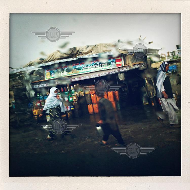 People hurry through the rain on a Kabul street.