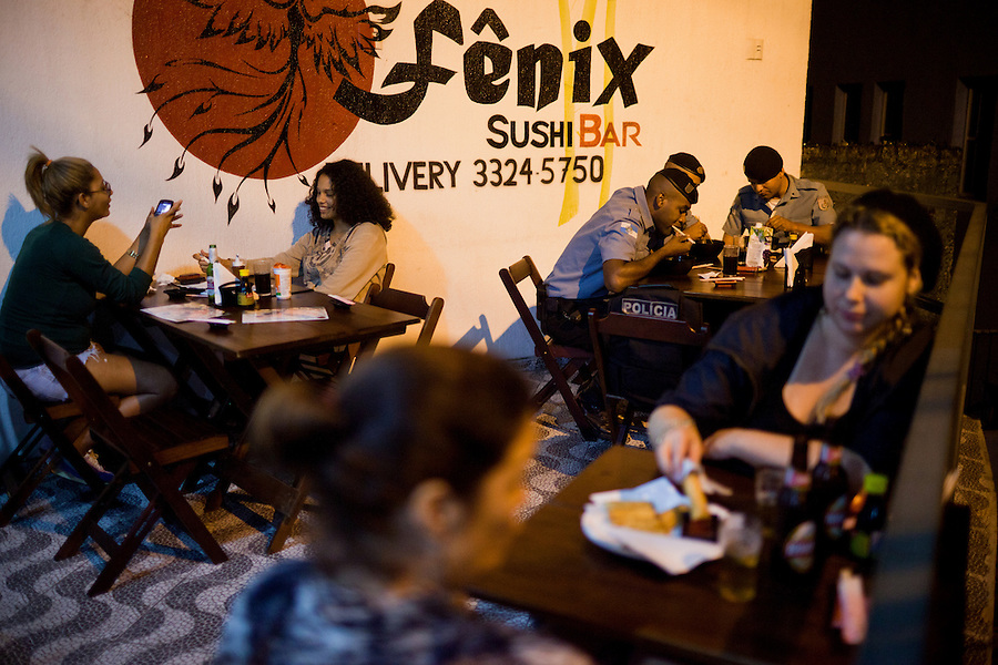 The Pacification Police, far left, (L-R: Tiago Silva, Jonothan Pinheiro, and Tiago Almeida) and local residents (far L-R: Rafaela Maia and Josanna Vaz) have dinner at Fenix Sushi Bar is just one of several new businesses opened since pacification that attracts many outsiders and foreigners in the community of Vidigal, in Rio de Janeiro, Brazil, on Sunday, May 19, 2013.