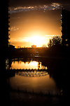 © Joel Goodman - 07973 332324 . No syndication permitted . 21/11/2013 . Manchester , UK . A fiery orange sunset over the River Irwell on the border between the two cities of Salford and Manchester , this evening ( Thursday 21st November 2013 ) as a commuter crosses a pedestrian footbridge from Salford to Manchester . Photo credit : Joel Goodman