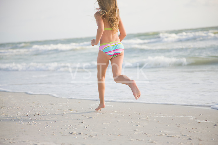 USA, Florida, St. Pete Beach, Rear view of girl (8-9) in bikini running on beach