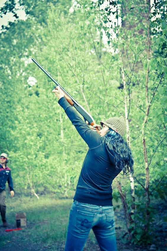 Professional mountain biker Tammy Donahugh shoots a shotgun while visiting Copper Harbor Michigan Upper Peninsula.