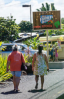 Local Hawai'i residents head to the lunch wagon at near the Hilo Farmers Market Kitchen sign on Mamo Street, Big Island of Hawai'i.