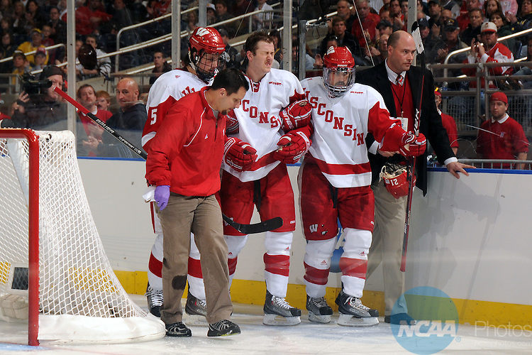 10 APR 2010: Wisconsin forward Derek Stepan (21) needs help from his teammates after crashing into the boards during the Division I Men's Ice Hockey Championship held at Ford Field in Detroit, MI. Boston College defeated Wisconsin 5-0 to win the national title game.  Mark Hicks/NCAA Photos