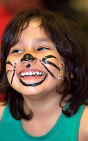 Girl age 5 at church soup kitchen with cat whiskers painted on face.  Minneapolis  Minnesota USA