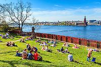 Park med människor som har picknik i Ivar Los park vid Monteliusvägen på Mariaberget vid Riddarfjärden med Stadshuset i Stockholm