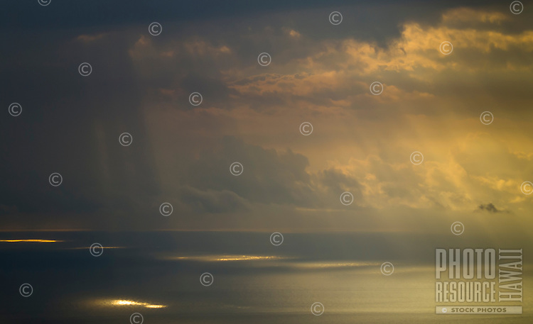 Sun rays beam through afternoon clouds onto calm ocean waters, viewed from the hillside of Hualalai volcanic mountain, Kailua-Kona, Big Island.