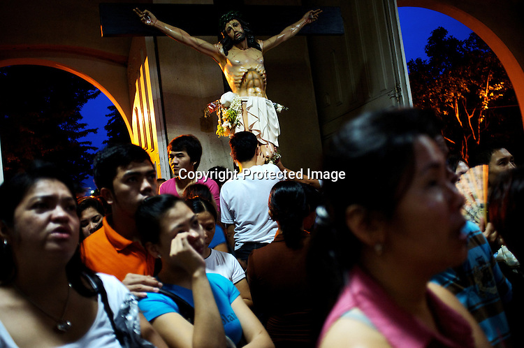 """Worshippers touch the statue of Jesus Christ on wednesday evening at the Redemptorist Church in Baclaran in Manila, Philippines. The Baclaran church is said to be the most attended church in Asia drawing up to 100,000 worshippers """" in Manila, Philippines. Photo: Sanjit Das"""