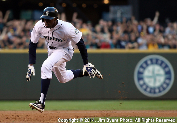 Seattle Mariners' James Jones rounds the bases before sliding head first into third base after hitting  a triple to center field in the third inning September 13, 2014 at Safeco Field in Seattle.The Athletics beat the Mariners 3-2 when Mariners pitcher Fernando Rodney  walked in Coco Crisp in the 10th inning.  ©2014. Jim Bryant Photo. All Rights Reserved.
