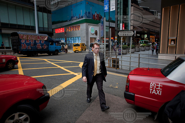 A businessman crosses the road in the business district of central Hong Kong.