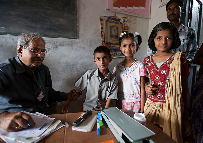 21 May 2013, Mandiganal Village, Karnartaka, India:  From left: Dr Bellada of the Karnataka Mobile Health Clinic project conducts a check up on Manoj Kottappa Dev Reddy (6), Rajeshwari (9) and Ashwini Ningaoda (10) in the Anganwadi centre at Mandiganal Village. The World Bank is financing the Karnataka Health Systems Project that is bringing mobile health clinics to remote villages in Karnataka and covers the cost of an ambulance, a doctor, pharmacist, two nurses, a cleaner and a driver. Villagers have the opportunity to see a doctor once a week for basic services and will be referred to Primary Health Care centres for larger issues Picture by Graham Crouch/World Bank