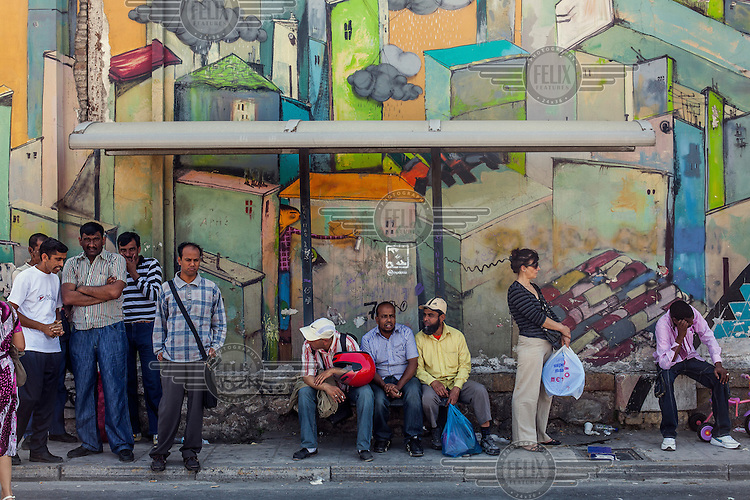 A group of migrants wait for the bus near a flea market.