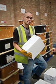 An ex-claimant of Job Seekers Allowance working in a warehouse on Stakehill Industrial Estate, Oldham, following a compulsory four week unpaid work placement, part of a Mandatory Work Related Activity welfare-to-work programme.