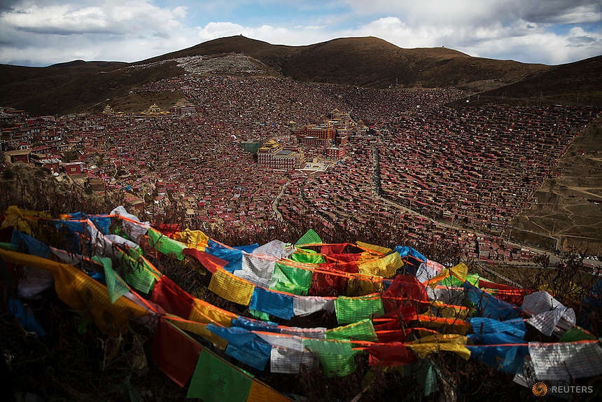 Tibetan prayer flags flutter above the Larung valley and its Larung Wuming Buddhist Institute, located some 3700 to 4000 metres above the sea level in remote Sertar county, Garze Tibetan Autonomous Prefecture, Sichuan province, China October 30, 2015. The Institute was founded in 1980 by Khenpo Jigme Phuntsok, an influential lama of Nyingma sect of Tibetan buddhism with only around 30 students but is now widely known as one of the biggest centres to study Tibetan Buddhism in the world. Today, tens of thousands monks and nuns live in small houses and log cabins surrounding the Larung Wuming Buddhist Institute. Picture taken October 30, 2015.   REUTERS/Damir Sagolj