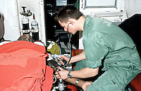 Paramedic ambulance crew attending to the victim of a heart attack in the back of an ambulance. They have the patient on oxygen and  an ecg machine to monitor his heart rate. The paramedic is also taking his blood pressure.