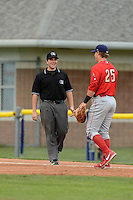 Umpire Mike Savakinas and Williamsport Crosscutters first baseman Logan Pierce (25) discuss a called foul ball during a game against the Batavia Muckdogs on September 4, 2013 at Dwyer Stadium in Batavia, New York.  Williamsport defeated Batavia 6-3 in both teams season finale.  (Mike Janes/Four Seam Images)