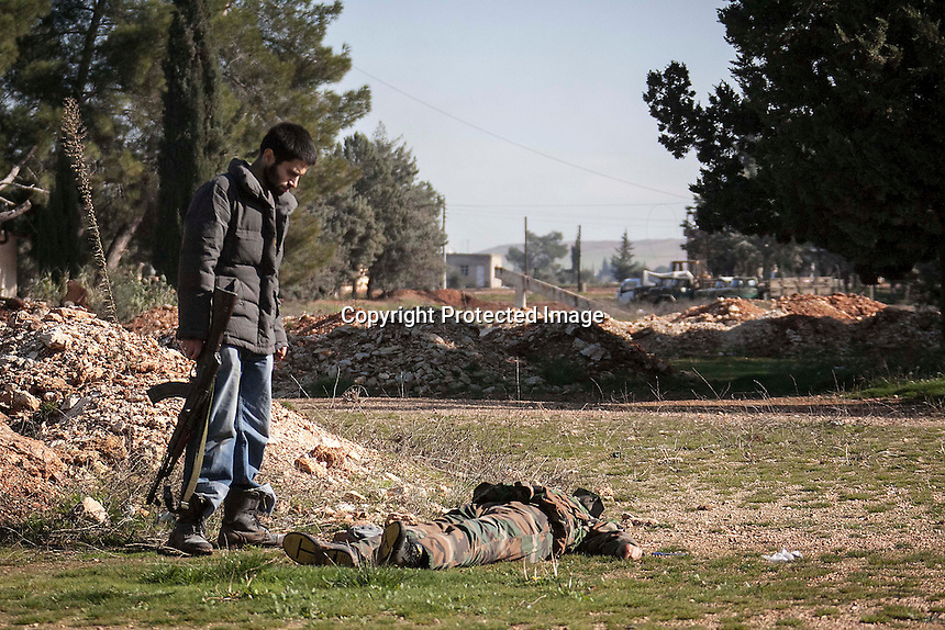 In this Saturday, Dec. 15, 2012 photo, a lifeless body of one pro-government soldier lays on the ground as a Syrian rebel fighter looks over the dead body after the soldier was killed during heavy clashes inside one militar academy besieged by rebels at the north of Aleppo, Syria. The Free Syrian Army took control over the Academy after several hours battling the troops loyal to President Bashar al-Assad. Among the casualities are one FSA General and one Syrian journalist. (AP Photo/Narciso Contreras)