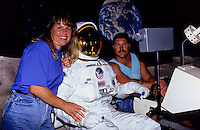 Astronaut in spacesuit posing with two visitors at the smithsonean museum in Washington DC, USA