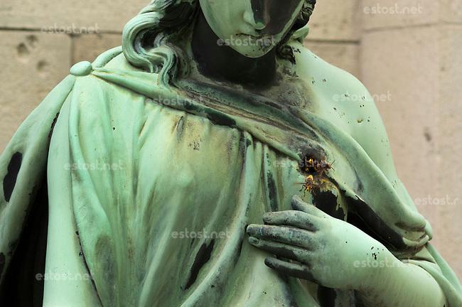UNGARN, 07.2017, Budapest - VIII. Bezirk. Kerepesi-Nationalfriedhof: Jugendstil-Statue mit Herzschuss, nun ist sie zum Hornissen-Nest geworden. | Kerepesi national cemetery: Art Nouveau statue shot in the heart. Now she has become the home of hornets. <br /> &copy; Martin Fejer/estost.net
