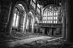 Disused and abandoned derelict church interior with gothic arches and stained glass window