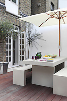 A white modular table and bench seats next to a parasol are set on a decked terrace in a town garden. Tableware and glassware are ready on the table for an outdoor lunch.