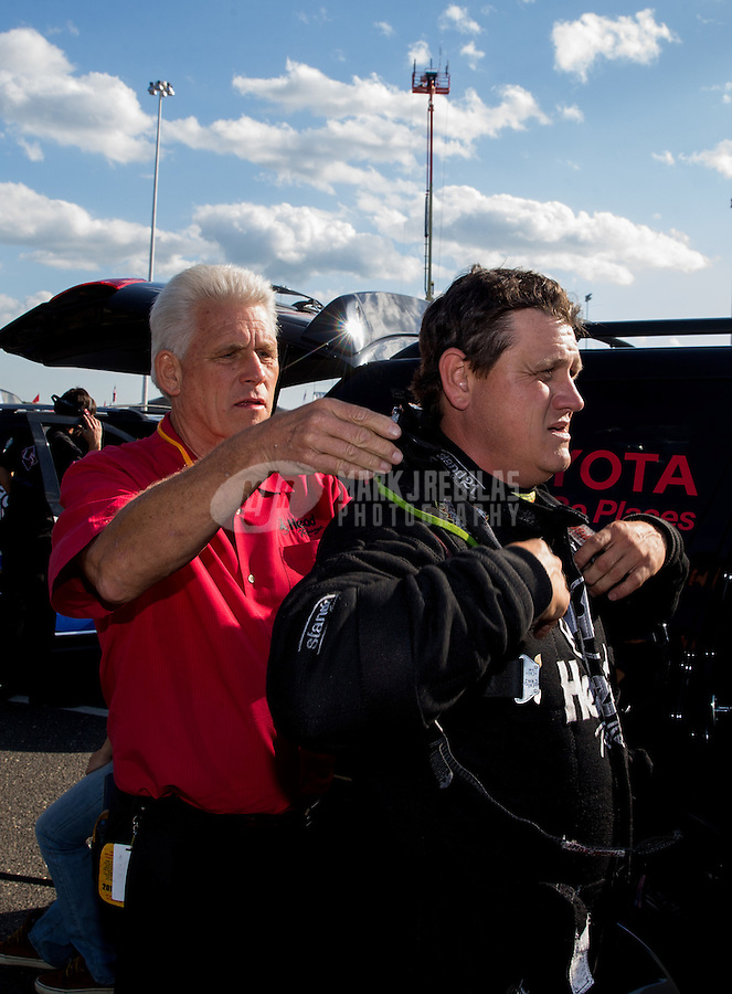 May 30, 2014; Englishtown, NJ, USA; Jim Head (left) helps his son NHRA funny car driver Chad Head during qualifying for the Summernationals at Raceway Park. Mandatory Credit: Mark J. Rebilas-