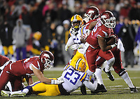 NWA Media/ANDY SHUPE - Arkansas' Jonathan Williams, right, carries the ball through the arms of LSU's Lamar Louis (23) during the second quarter Saturday, Nov. 15, 2014, at Razorback Stadium in Fayetteville.