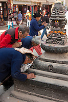 Bodhnath, Nepal.  Worshipers Pray at a Shrine at the Base of the Bodhnath Stupa, a Tibetan Buddhist Stupa.