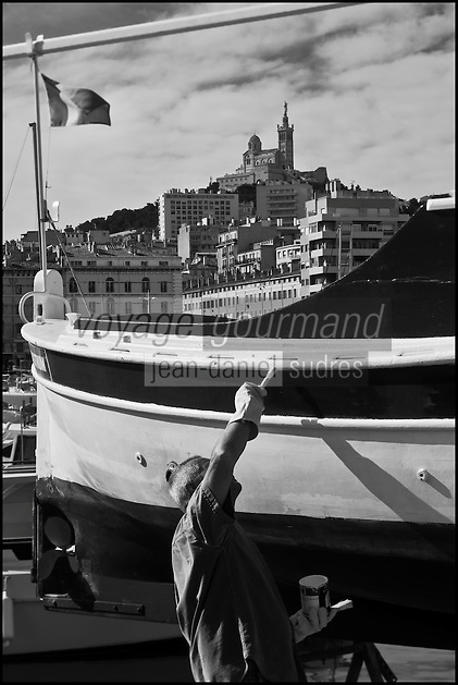 Europe/France/Provence-Alpes-Côte d'Azur/13/Bouches-du-Rhône/Marseille: Le Vieux Port -Pêcheur repeignant son pointu et Notre Dame de la Garde